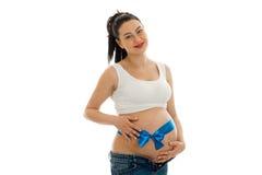 Porträt des schwangeren Brunette im weißen Hemd mit blauem Band auf ihrem Bauch, der auf der Kamera lokalisiert auf Weiß schaut u Lizenzfreie Stockfotografie