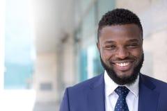 Porträt des schwarzen lächelnden Geschäftsmannes, der Kamera in einer städtischen Landschaft betrachtet Kopieren Sie Platz stockbilder