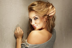 Porträt des sexy blonden Mädchens, das Kamera und das Lächeln betrachtet Stockfotografie