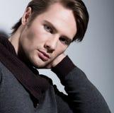 Porträt des sexy jungen Mannes mit der Hand nahe Gesicht. Lizenzfreie Stockfotos