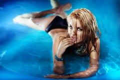 Porträt des sexy jungen weiblichen Genießens im Swimmingpool. Stockfotografie
