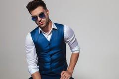 Porträt des sexy Mannes eine blaue Weste und Sonnenbrille tragend Stockfotos