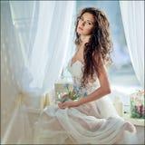 Porträt des sinnlichen gelockten behaarten Mädchens in einem weißen Kleid gegen t stockfotos