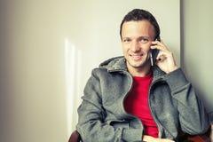Porträt des Sitzens des jungen Mannes, der am Handy spricht Lizenzfreie Stockfotografie