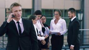 Porträt des SmartstadtGeschäftsmannes, der auf dem Telefon und den Geschäftsleuten im Hintergrund die Genossenschaft besprechend  stock video