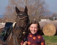 Porträt des smilling Mädchens mit ihrem Sportpony vor Wettbewerb Stockfoto