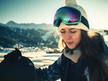 Porträt des Snowboardermädchens auf dem Hintergrund des hohen Berges Stockfoto