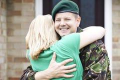 Porträt des Soldaten Hugging Wife Home auf Urlaub von der Armee stockfotografie