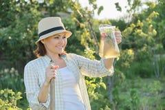 Porträt des Sommers im Freien der Frau mit dem natürlichen Getränk gemacht von den Erdbeertadellosen Kräutern, Frauengartenarbeit stockfotografie