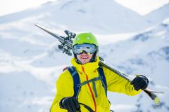 Porträt des sportiven Mannes im Sturzhelm mit Skis auf seiner Schulter Lizenzfreies Stockbild