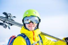 Porträt des sportiven Mannes im Sturzhelm mit Skis auf seiner Schulter Stockfotos