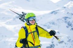 Porträt des sportiven Mannes im Sturzhelm mit Skis auf seiner Schulter Lizenzfreie Stockfotos