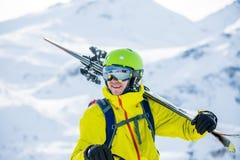 Porträt des sportiven Mannes im Sturzhelm mit Skis auf seiner Schulter Stockbilder