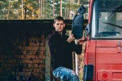 Porträt des Stands des jungen Mannes auf Seite auf LKW-Kabine lizenzfreies stockfoto