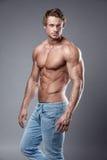Porträt des starken athletischen Eignungsmannes über grauem Hintergrund stockfotos