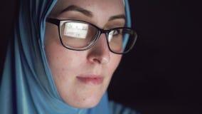 Porträt des starken Gesichtes der moslemischen Frau im hijab und der Gläser nachts in den dunklen Suchen das Internet stock footage