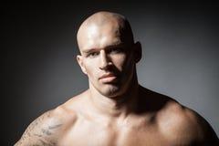 Porträt des starken Mannes lokalisiert auf Dunkelheit Lizenzfreies Stockbild