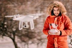 Porträt des Steuerungsdrohne des Mannes über Hügeln und Wald - Videography- und Luftbildfotografiekonzept lizenzfreies stockfoto
