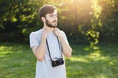 Porträt des stilvollen bärtigen Mannes mit der Retro- Kamera, die am grünen Park untersucht Abstand mit durchdachtem Ausdruck ste Stockbilder