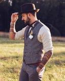 Porträt des stilvollen Bartes, Mann mit Tätowierungen auf seinen Armen Die Braut- und Bräutigamhintergrundblumenverzierung Lizenzfreie Stockbilder