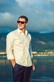 Porträt des stilvollen dunkelhaarigen jungen Mannes in der Sonnenbrille an der Küste lizenzfreie stockfotografie