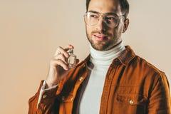 Porträt des stilvollen jungen Mannes, der Parfüm anwendet stockfoto