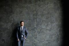 Porträt des stilvollen Mannes kleidete in einer Klage über grauem Hintergrund an stockbilder