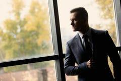 Porträt des stilvollen Mannes kleidete in einer Klage über grauem Hintergrund an lizenzfreies stockfoto