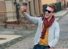 Porträt des stilvollen modernen jungen Mannes, der auf der Straße bleibt Stockfoto