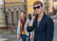 Porträt des stilvollen modernen jungen Mannes, der auf der Straße bleibt Stockfotos