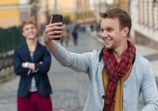 Porträt des stilvollen modernen jungen Mannes, der auf der Straße bleibt Stockbilder