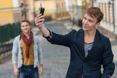 Porträt des stilvollen modernen jungen Mannes, der auf der Straße bleibt Stockbild