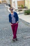 Porträt des stilvollen modernen jungen Mannes, der auf die Straße geht Stockfoto