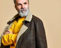 Porträt des stilvollen Reichers des Ältesten mit einem Bart und des Schnurrbartes in einem ledernen Wintermantel stockfoto