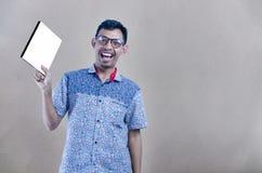 Porträt des Studenten unter Verwendung der Gläser, die mit Buch von Fotografie stehen stockfotos
