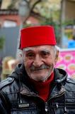 Porträt des türkischen Seniors trägt Fez und Lederjacke lächelt Lizenzfreie Stockfotografie