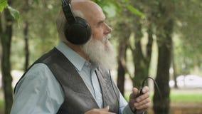 Porträt des Tanzens des älteren Mannes hört Musik mit Kopfhörern stock video