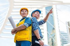 Porträt des Teampartnerwirtschaftsingenieurs, der zum Kameraabnutzungsschutzhelm mit Holdinginspektion steht und schaut stockfoto