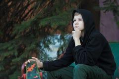 Porträt des Träumens des Jugendskateboardfahrers, der nach vorn schaut stockfoto