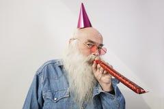 Porträt des tragenden Parteihutes des älteren Mannes beim Schlag des Horns gegen grauen Hintergrund Lizenzfreie Stockfotografie