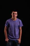 Porträt des tragenden T-Shirts des jungen Mannes, welches die Kamera betrachtet Stockfoto