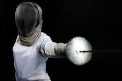 Porträt des tragenden weißen fechtenden Kostüms der Fechterfrau, das mit der Klinge übt Getrennt auf schwarzem Hintergrund Stockfoto