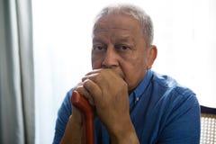 Porträt des traurigen älteren Mannes, der gehenden Stock beim Sitzen auf Stuhl hält Stockfotografie