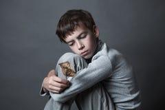 Porträt des traurigen Jugendlichen auf grauem Hintergrund, Stockfotos