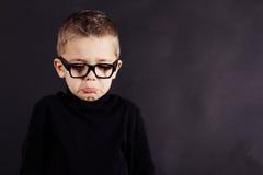 Porträt des traurigen Kindes im Pullover und in den Gläsern Stockfotografie