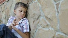 Porträt des traurigen kleinen Jungen draußen zur Tageszeit stock video