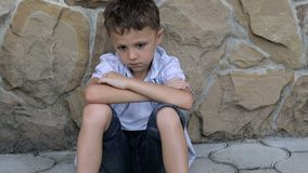 Porträt des traurigen kleinen Jungen draußen zur Tageszeit stock footage