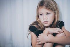 Porträt des traurigen kleinen Mädchens, das nahe dem Fenster sitzt Lizenzfreies Stockbild