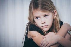 Porträt des traurigen kleinen Mädchens, das nahe dem Fenster sitzt Stockfotos