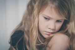 Porträt des traurigen kleinen Mädchens, das nahe dem Fenster sitzt Stockbilder